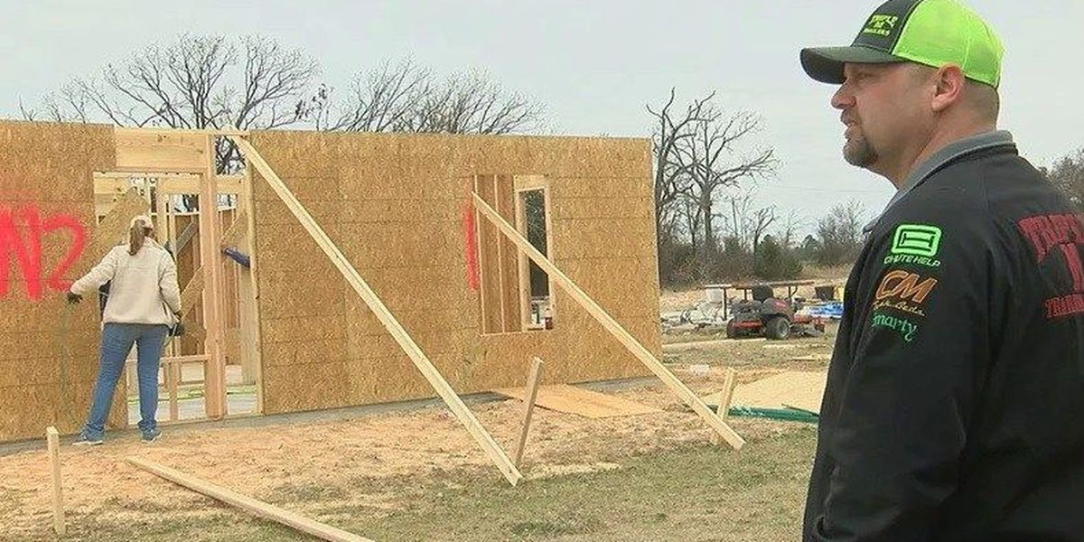 Volunteers work on officers' new house, after it was destroyed by tornado